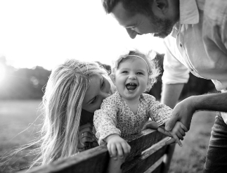 happy family in a field with a toddler